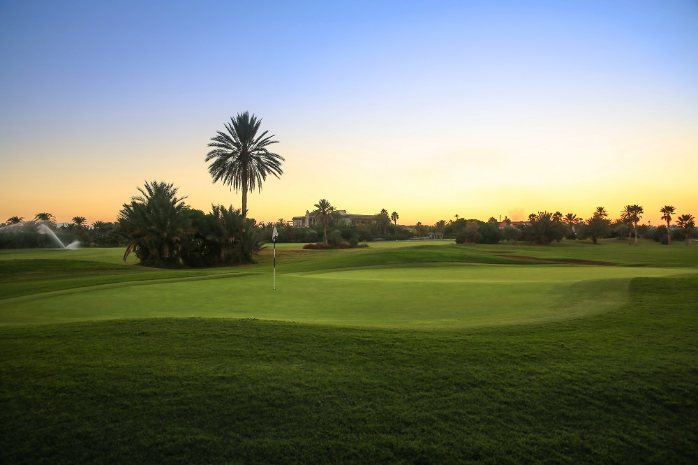Large green et coucher de soleil sur le parcours Palm Golf Palmeraie à Marrakech