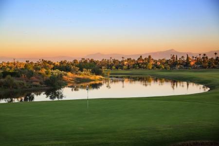 Large green; obstacle d'eau et montagnes sur le parcours Palm Golf Palmeraie Marrakech