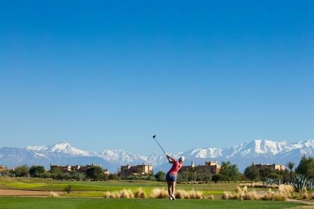 Un joueur et les montagnes de l'Atlas sur le golf de Samanah.