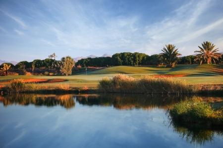 Large obsatcle d'eau et green sur le parcours de golf de La Palmeraie à Marrakech au Maroc